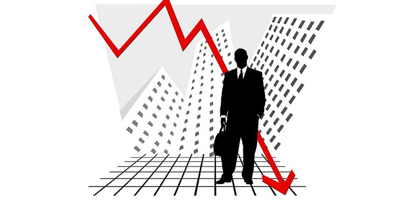 Uomo d'affari con freccia rossa del grafico che va in basso